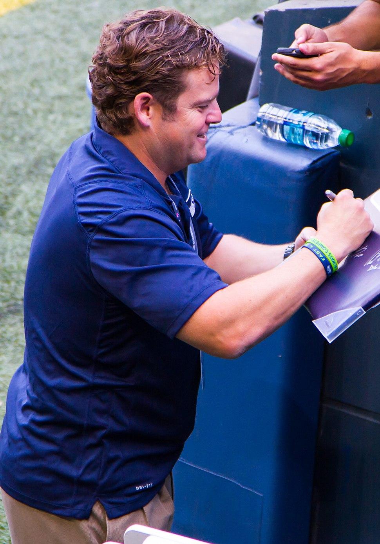 Candid waist-up photograph of Schneider wearing a blue shirt and signing an autograph.