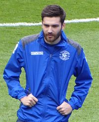 White man with dark hair and beard wearing sports kit