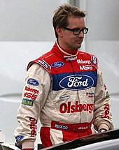 Man in his mid forties, wearing white, blue and red racing overalls. He has a head full of hair and is wearing glasses.