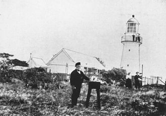 Bustard Head Light - Lighthouse keeper, M. J. Rooksley in front of the lighthouse and the original cottages, 1902