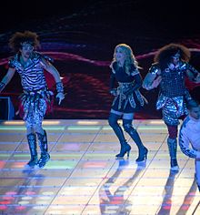 Madonna, in high heels, dancing onstage with three other people