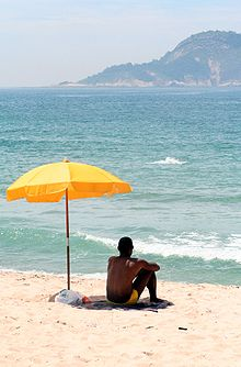 Man sitting under a beach umbrella