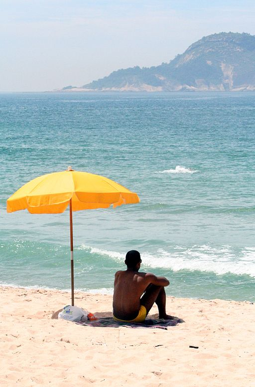 Man sitting under beach umbrella