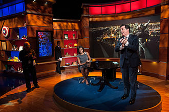 Stephen Colbert - Colbert, in his television series persona, prepares to interview Michelle Obama. The set of The Colbert Report satirized cable-personality political talk shows.