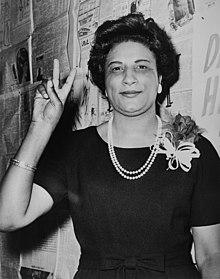 Pani Constance B. Motley, pierwsza kobieta Senator, 21. Okręg Senatorski, NY, podnosząca rękę w znaku V.jpg