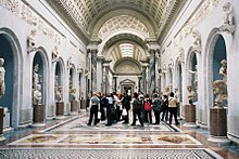 Photo of a gallery in the museum. It is in the Classical style and has a wide arched roof with skylights. The colour scheme is are blue-grey and white with a polychrome marble floor. The walls of each side of the gallery have a row of large niches in which stand marble statues. Between the niches are plinths supporting smaller portrait sculptures.
