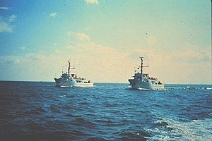 NOAAS Rude (S 590) - Rude (left) worked with her sister ship ''Heck'' (S 591) (right) on wire drag operations until 1989.