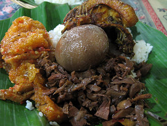 Javanese cuisine - Javanese complete nasi gudeg, which consist of (from top clockwise):krechek (spiced buffalo skin cracker), ayam goreng (fried chicken), opor telur pindang (spiced egg in coconut milk), and gudeg (young jackfruit cooked in coconut milk). Gudeg is one of the most famous Javanese dishes.