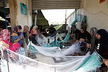 Women sitting in a circle, sewing fishing nets