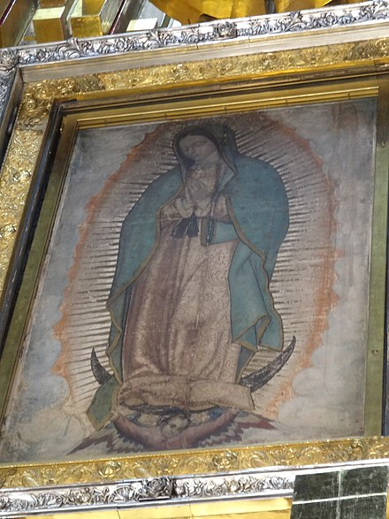 Our Lady of Guadalupe, patron saint of Mexico, an ancient Marian title of Amerindian race. This painting of her at the Basilica of Guadalupe is among her most notable depictions; scientists still debate if it should be dated 1531, the year of the first apparition, or the 1550s. Nueva Basilica de Nuestra Senora de Guadalupe (JC) 01.JPG