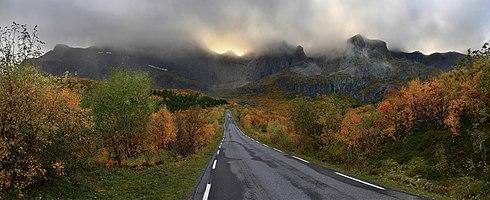 A road (Fylkesvei 807) in Flakstadøya island in the Lofoten in autumn. The mountain massif in the background contains summits such as Stjernhauet, Stjerntinden, Bjørntinden...