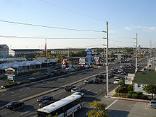 A wide, busy, divided highway is flanked by hotels, restaurants, and other businesses serving beach visitors.