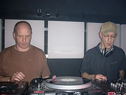 Two men perform music using various mixing boards and turntables.