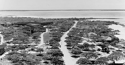 "Aerial view of Pan American Airways Hotel and facilities on Peale Island at Wake Atoll. The hotel is on the left, the anchor from the Libelle shipwreck and the pergola leading to the ""Clipper"" seaplane dock is on the right. PAA Hotel and facilities at Wake Island.jpg"