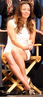 Linda seated with group, in director's chair, in white sleeveless mini and silver closed heels