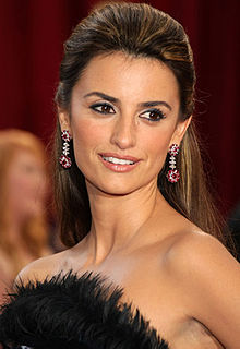 The photo shows a close-up of a Hispanic woman with her brown highlight hair clipped behind her ears. The female is wearing eyeliner and lipgloss as well as pink and white colored dangling earrings on both her ears. She is wearing a strapless black dress with black feathers. In the background, a blonde female can be seen as well as a red curtain.