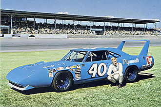 Pete Hamilton - Pete Hamilton squatting next to the 1970 Plymouth Superbird he drove to victory in 3 of the 1970 season SuperSpeedway races.
