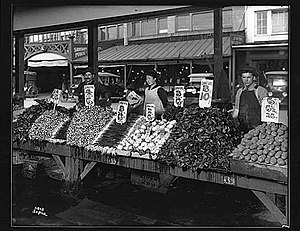 History of the Pike Place Market - Vegetable vendors selling from Main Arcade daystalls, 1917. Part of the Sanitary Market and Corner Market are visible across Pike Place.