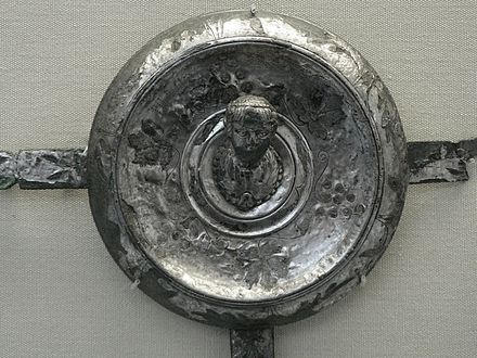 "One of the Xanten Horse-Phalerae located in the British Museum, measuring 10.5 cm (4.1 in). It bears an inscription formed from punched dots: PLINIO PRAEF EQ; i.e. Plinio praefecto equitum, ""Pliny prefect of cavalry"". It was perhaps issued to every man in Pliny's unit. The figure is the bust of the emperor. Plinio praefecto.jpg"