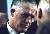 Headshot of a greying man in a suit who is indirectly facing the camera as he listens to a man a portion of whose head is shown from its side-to-rear