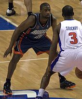 A black person wearing a dark-color jersey defends against another person in white jersey who dribbles in front of him
