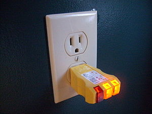 Receptacle tester - A receptacle tester being used to verify the proper wiring of an outlet. For this particular tester, proper wiring is indicated by the two yellow lights.