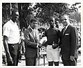 Satch Sanders of the Boston Celtics, Roxbury District Court Judge Elwood S. McKenney and Police Commissioner Edmund McNamara stand with a young man holding a basketball trophy (13561738835).jpg