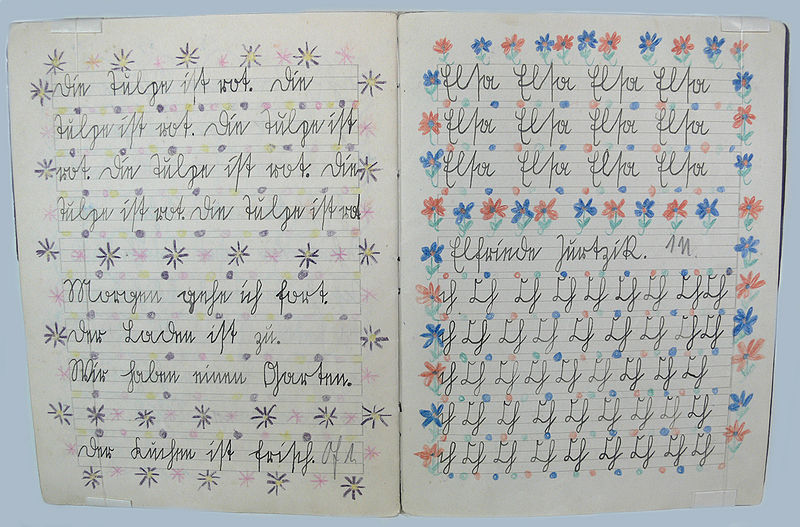 This picture shows an opened, colorfully decorated exercise book with writing exercises in Sütterlin script.