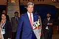 Secretary Kerry carries flowers given to him after arriving in India for Vibrant Gujarat Summit.jpg