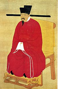 A portrait oriented scroll depicting a man with a pointy beard and mustache in thick red robes, black pointed shoes, and a square cut, black hat with long, thin protrusions coming out horizontally from the bottom of the hat, sitting on a throne.