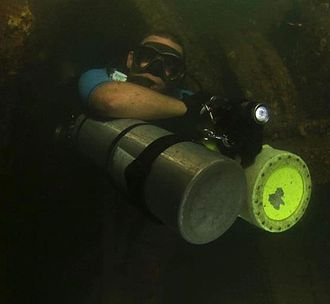 Sidemount diving - Sidemount diver partially removes (forward rotates) both primary cylinders to permit passage through a restriction in a wreck.