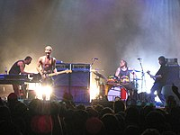 A rock band, Silverchair, performing onstage. From left to right, keyboardist playing a synthesizer, a drummer playing drumkit, a singer with short blonde hair and no shirt (also playing electric guitar), and a bass guitarist.