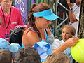 Sorana Cîrstea signing autographs for ball boys and girls at the 2011 BCR Open Romania Ladies.jpg
