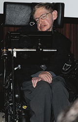 A colored photograph of a man, sitting in an wheelchair with his arms folded. He is wearing glasses and is looking from left to right.