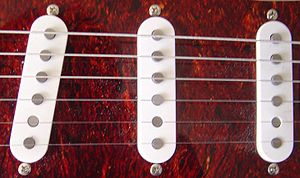 Single coil guitar pickup - This image shows three single coil pickups on a Stratocaster guitar. Left to right: bridge, middle and neck pickups.