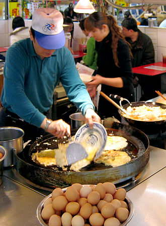 Oyster omelette - A hawker is making oyster omelette in the Shilin Night Market of Taipei.