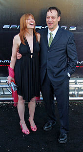 A man standing with a woman at a film premiere.