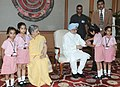 The school children tying 'Rakhi' to the Prime Minister, Dr. Manmohan Singh, on the occasion of 'Raksha Bandhan', in New Delhi on August 21, 2013. Smt. Gursharan Kaur is also seen (2).jpg