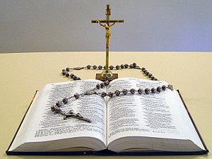 Rosary - The most commonly known format of the Rosary, flanked by the Bible and a free-standing crucifix.