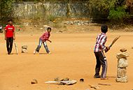 Three Hyderabadi boys playing with cricket bats and a ball