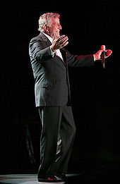 Tony Bennett is opening his arms, and holding a mic in his hand.