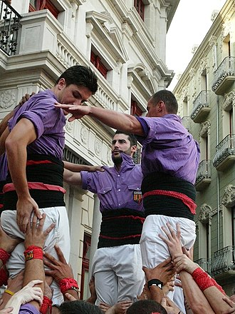 Castell - Three castellers in Reus wearing traditional uniforms with white pants and a sash used as a support and handhold.
