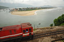 In the foreground, a red diesel locomotive is travelling up a mountain against the backdrop of Lang Co Beach and the sea. In the background are the mountains.