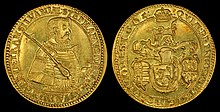 A golden coin depicting an armored middle-aged man on one side, and a coat-of-arms on the other side