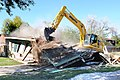 U.S. Air Force Tech. Sgt. Carl White Jr., with the 147th Civil Engineer Squadron (CES), Texas Air National Guard, operates heavy equipment to demolish a drug house in Harlingen, Texas, Dec. 16, 2013 131216-Z-BQ644-005.jpg