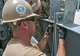 U.S. Navy Builder 2nd Class Drake Van Blarcom, left, and Steelworker 1st Class Antonio Chavezplata, both assigned to Construction Battalion Maintenance Unit 303, bolt together a metal structure during 130402-N-WX059-134.jpg