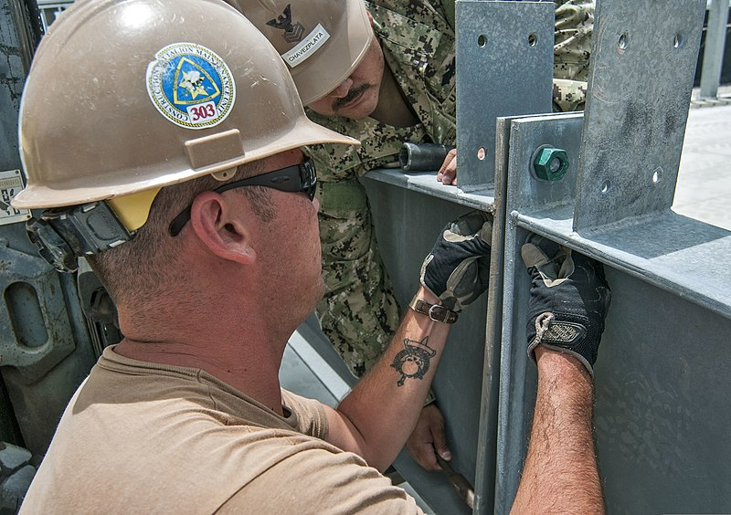File:U.S. Navy Builder 2nd Class Drake Van Blarcom, left, and Steelworker 1st Class Antonio Chavezplata, both assigned to Construction Battalion Maintenance Unit 303, bolt together a metal structure during 130402-N-WX059-134.jpg