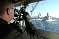 US Navy 030226-N-6141B-003 A crew member on the ship's bridge use a sextant style stadimeter-range finder to verify distance between ships during a replenishment at sea operation.jpg