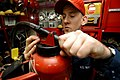 US Navy 040405-N-6278K-053 Damage Controlman Fireman Justin Tassey, of Butler, Pa., inspects a potassium bicarbonate dry chemical (PKP) fire extinguisher in one of ten major repair lockers aboard USS George Washington (CVN 73).jpg