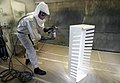 US Navy 040413-N-5328N-029 A U.S. Air Force Airman spray paints a piece of equipment in a paint booth at Naval Air Technical Training Command (NATTC).jpg
